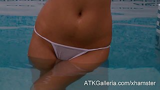 Buxom babe at the indoor pool pleasures her wet pussy