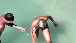 Blonde nudist chick swimming in the water