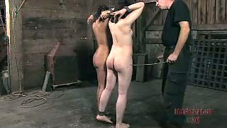 Two brunette girls get whipped in a barn in BDSM video
