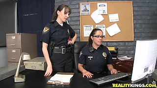 Two female police officers get ass fucked in an interrogation room