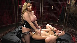 Busty dominatrix has fun with helpless slave in basement