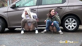 Two European amateur skanks pissing behind the car