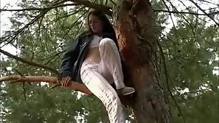 Amateur brunette is on a tree and peeing