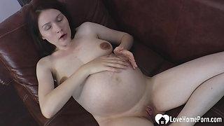 Brunette pregnant babe caresses her big tummy