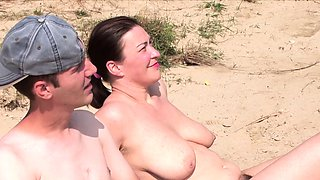 Busty MILF with natural tits fucks on the beach