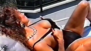 Stunning redhead vintage milf beauty on the lounger by the pool