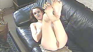 Quite flexible straight haired brunette brags of her nice soles on the sofa