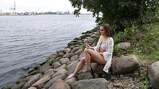 Beautiful brunette touches her big tits by the river